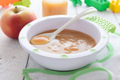 Apple puree in bowl on white table Stock Image