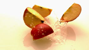 Apple quarters falling and bouncing on white wet surface stock footage