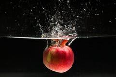 Apple que cae en agua Imagen de archivo libre de regalías