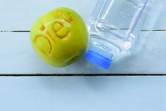 Apple que cinzela o caráter faz dieta e garrafa de água no fundo azul Vista superior Foto de Stock Royalty Free