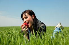 Apple que come a la muchacha en hierba verde Fotografía de archivo libre de regalías
