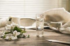Apple ramifica con las flores blancas y la bufanda ligera en una tabla de madera de la tabla Imágenes de archivo libres de regalías