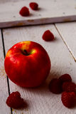 Apple and raspberries. On rustic wooden table, selective focus Stock Photography