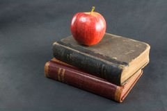 Apple and readers vertical. An apple on a stack of antique readers stock photos