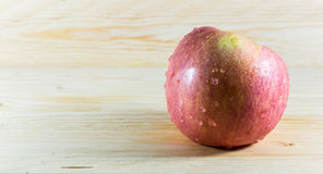 Apple. Red apple with drop on wooden background Stock Photo