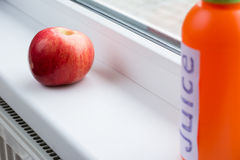 Apple red, fresh and ripe near the window. Red apple on a window sill and bottle of juice. Daylight Stock Photo