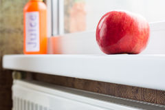 Apple red, fresh and ripe near the window. Red apple on a window sill. Daylight Stock Images