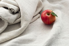 Apple. Red apple lying on a wooden table next to a burlap Royalty Free Stock Photos
