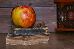 Apple is red on a pile of old books. Close-up Royalty Free Stock Photos
