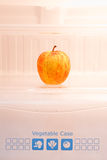 Apple in refrigerator Stock Images
