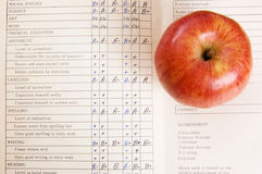 Apple on report card. A red apple on top of a vintage report card Royalty Free Stock Photo