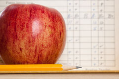 Apple and report card. Red apple on a book with pencil and vintage report card in background Stock Image