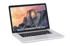 Apple retina de MacBook Pro de 15 pulgadas con OS X Yosemite en el tilte Imagen de archivo libre de regalías