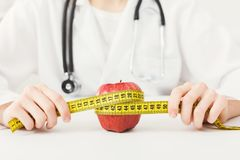 The apple is rewound by measuring tape by dietician. The apple is rewound by a measuring tape by a dietician. Healthy eating, right nutrition and slimming royalty free stock image