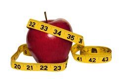 Apple rojo brillante con la cinta métrica amarilla Foto de archivo libre de regalías