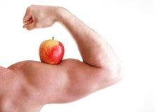 Apple rojo en el músculo de Bicep del hombre Imagen de archivo libre de regalías