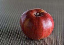 Apple rojo en el material gris Imagen de archivo