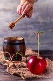 Apple rojo y un barril con la miel Foto de archivo