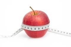 Apple rosso con nastro adesivo di misura su bianco Fotografie Stock Libere da Diritti
