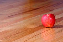 Apple rosso sul pavimento di legno duro Fotografia Stock