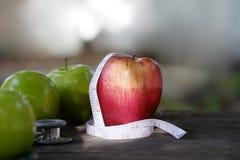 Apple rot und grün mit Maßband auf hölzernem Schreibtisch Lizenzfreie Stockfotos