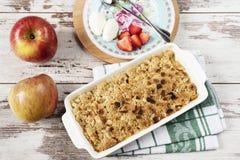 Apple rozdrobni deser z truskawkami i waniliową śmietanką na nieociosanym drewnianym tle fotografia stock