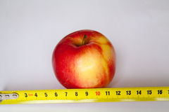 Apple with a ruler Stock Images