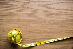 Apple and ruler on table Stock Photography