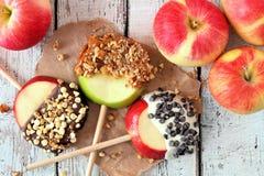 Apple rundor doppade med choklad och karamell, över på vitt trä royaltyfri foto