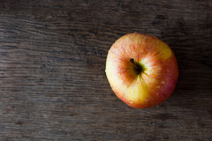 Apple on rustic wooden tabletop. Single apple with drops of water on rustic  wooden table top Royalty Free Stock Photography