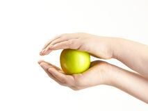 Apple sandwiched between childs hands Royalty Free Stock Photography