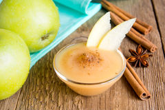 Apple sauce with cinnamon. Fresh homemade applesauce (apple puree, babyfood) with cinnamon (spices) and apples on wooden table close up, horizontal royalty free stock images