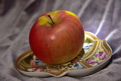 Apple on a saucer royalty free stock image