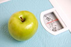 Apple on a scale. Green apple on a scale - diet Royalty Free Stock Image