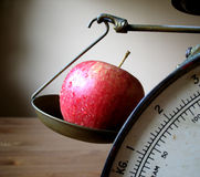Apple on Scale. What is the weight of life Royalty Free Stock Image