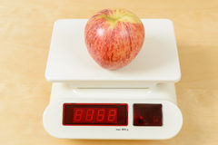 Apple on scale Royalty Free Stock Photography