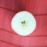 Apple-Scheibe auf rotem Stroh Stockfotografie