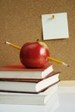Apple on school books stock image