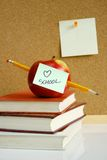Apple on school books. An apple on school books with pencil, post-it notes and cork board stock photos