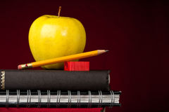 Apple and School Supplies. Stacked Books, school supplies, and an apple on top with a red background and space on the right for your text stock photos