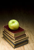 Apple and school textbooks. Green apple on pile of school books Royalty Free Stock Images
