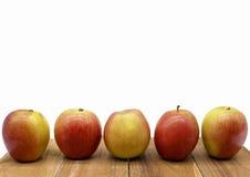 Apple se alinea en el bloque de madera Fotografía de archivo libre de regalías