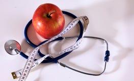 Apple se trouvant sur une table avec un stéthoscope et une bande de mesure Image stock