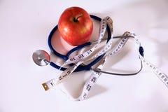 Apple se trouvant sur une table avec un stéthoscope et une bande de mesure Images libres de droits