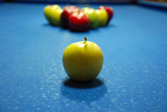 Apple shaped billard balls. On the blue billard table Royalty Free Stock Photos
