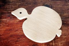 Apple-shaped chopping board on wooden background stock photography