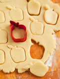 Apple shaped cookie cutter on raw cookie dough Royalty Free Stock Image