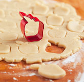 Apple shaped cookie cutter on raw cookie dough. Stock Photography