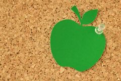 Apple shaped paper note on pinboard. Apple shaped paper note on cork pinboard Royalty Free Stock Image
