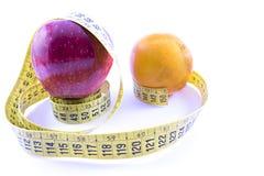 Apple, sinaasappel en centimeter stock foto